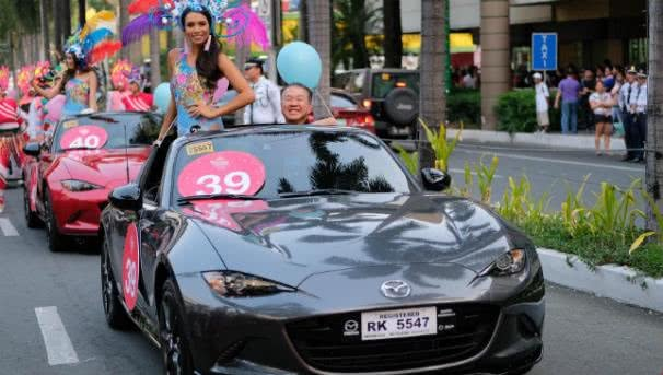 A beauty contestant standing in a mazda MX-5 smiles to the crowd at the 2017 Binibing Pilipinas pageant