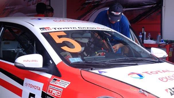 a man checking his racing car