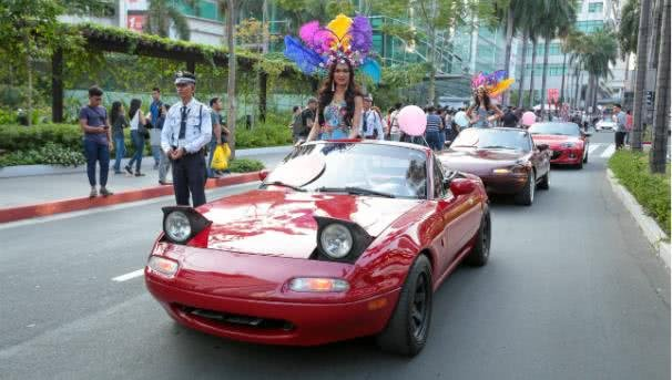 A beauty contestant in a mazda MX-5  smiles to onlookers at the 2017 Binibing Pilipinas pageant