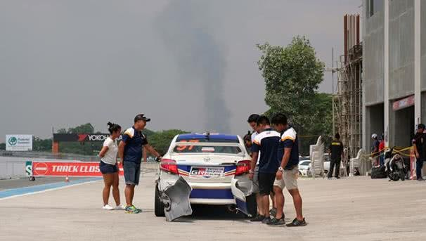 People are checking a clearly broken racing car
