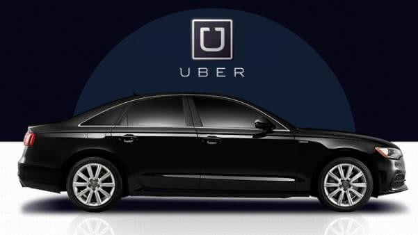 A black car in front of Uber backdrop