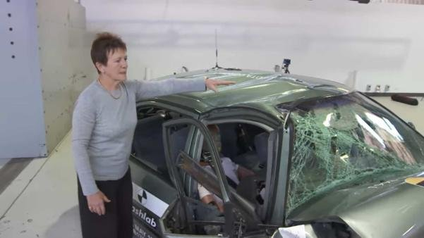 A woman standing next to a seriously damaged 1998 Corolla