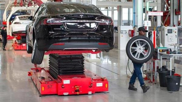 An engineer is carrying a wheel in Tesla automobile assembly plants