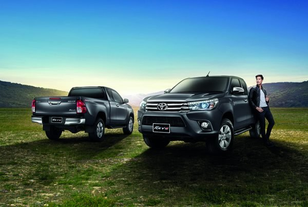 A boy with two models of the Toyota Hilux Revo