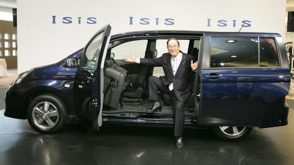 a man in suit opening the sliding door of a Toyota Isis