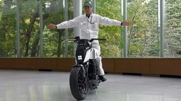 A man riding on a honda self-balancing motorcycle