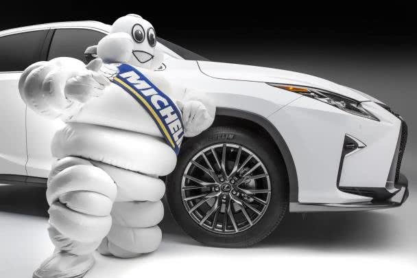 the Michelin Man standing next to a white car