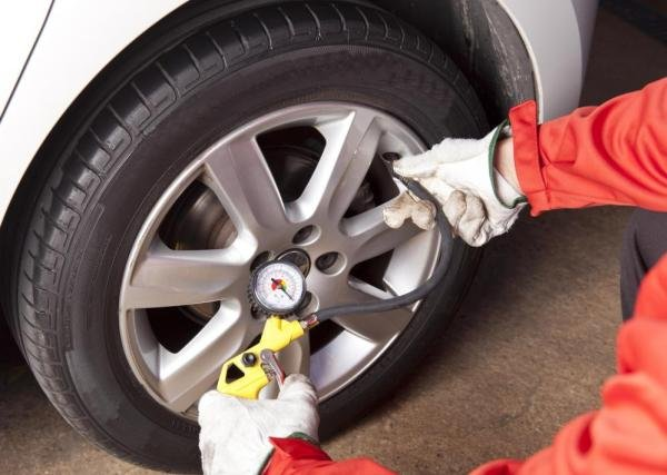 A car mechanic is inflating car tire