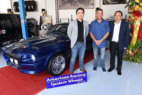 Three men standing beside a blue car at inauguration of Auto Options in Quezon City