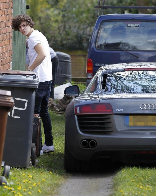 Harry Styles standing next to his Audi R8