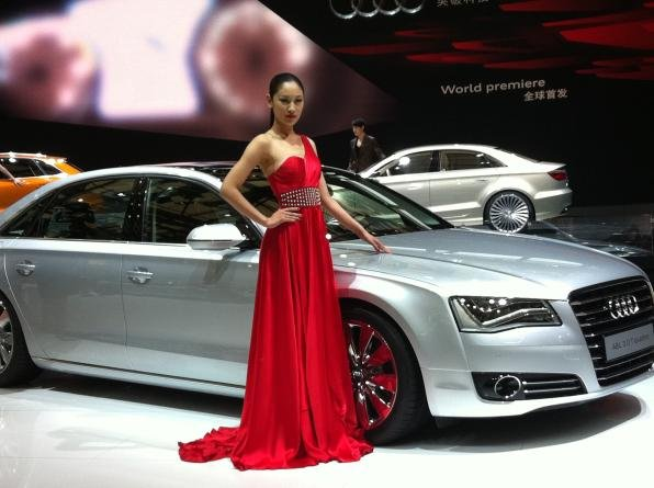 a promotion girl standing next to the Audi A8