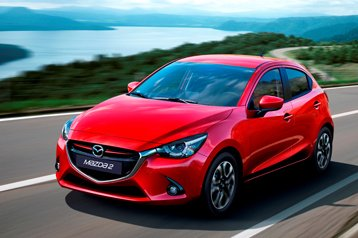 A red mazda 2 on the road