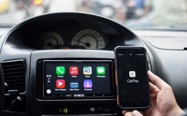 A phone with Apple Carplay in front of a dashboard