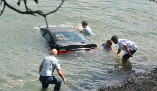 people escaping from a car floating on water