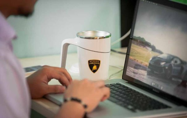 A man using his laptop and a Petron Lamborghini Anti-Spill Mug
