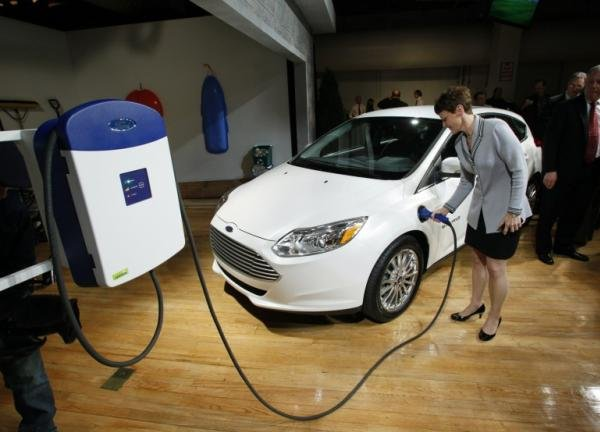 a woman is filling up the gas tank of a Ford Focus Electric