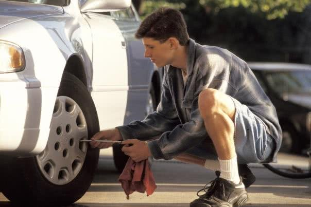 A man is checking his car's tires