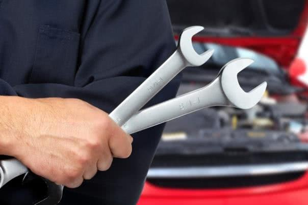 A man holding 2 wrenches in front of a car