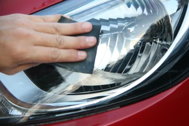 Cleaning headlight of a red car
