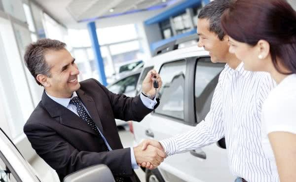 A car salesman is making a car deal with a couple