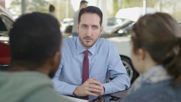 A car salesman is talking in front of two customers