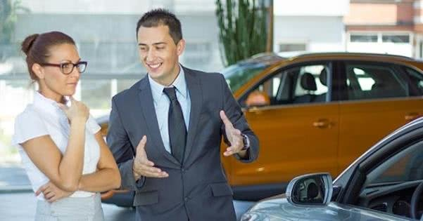 A car salesman introducing cars for his customer