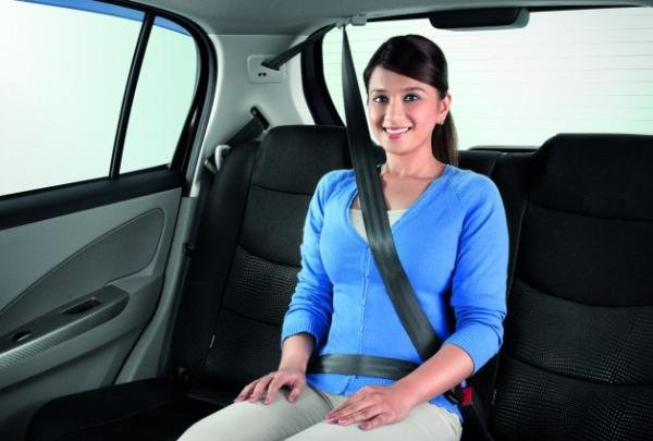 A woman wearing the 3-point seatbelt in a car