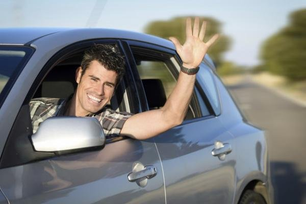 A man waving his hand from a car