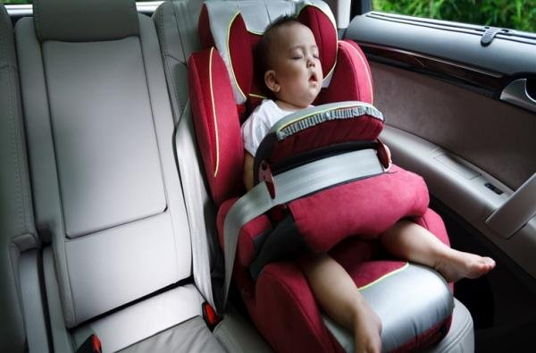 a child sleeping alone in a car