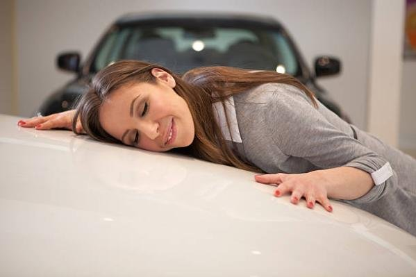 a girl hugging a car