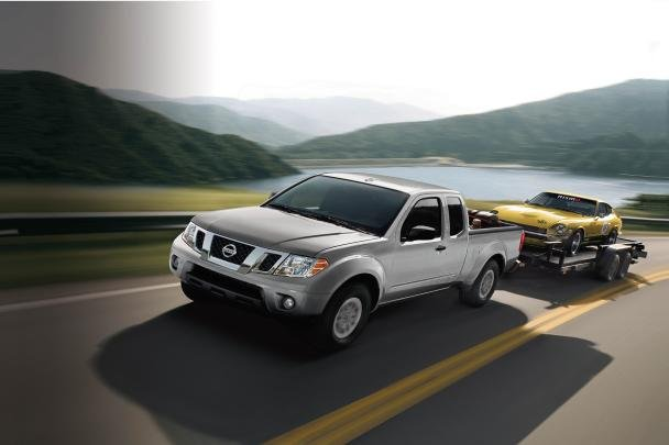 Nissan Frontier towing a coupe on the road