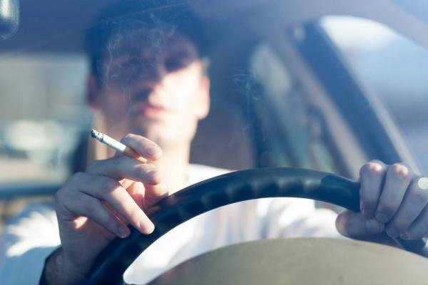 A man smoking in car while driving