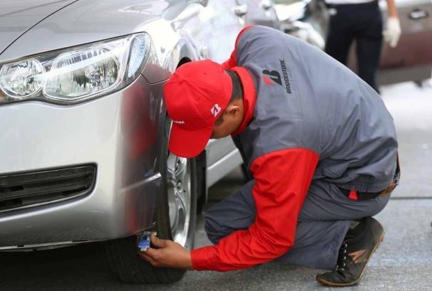 A car mechanic checking a car tire