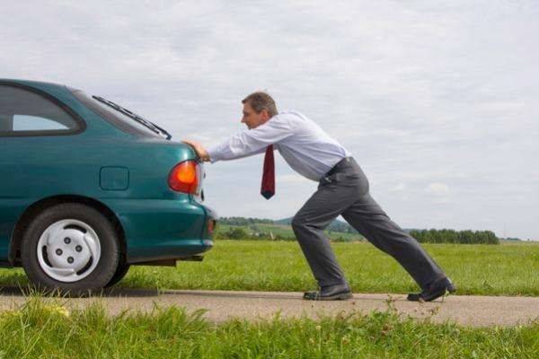 A man pushing a car