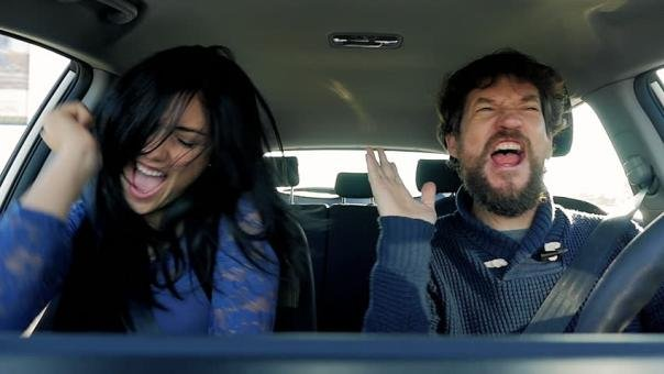 A man and woman dancing in a car