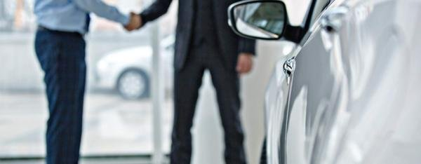 Two men shaking hands at car dealership