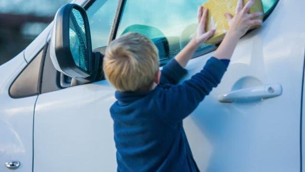a child cleaning a car