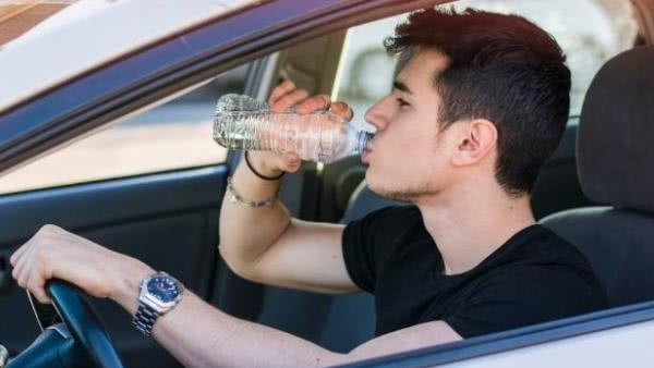 a men drinking water from a plastic bottle in a car