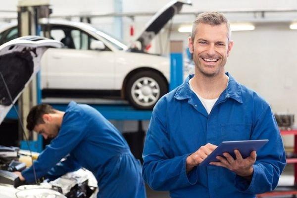 two mechanics inspecting a car