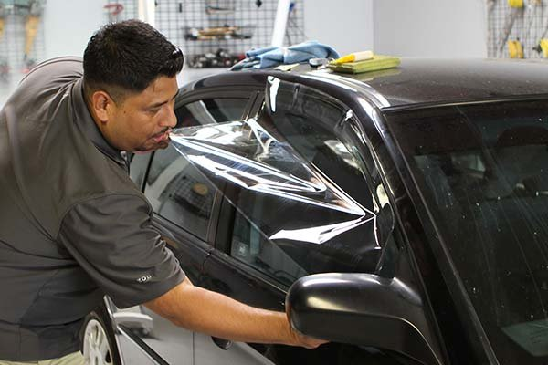 a mechanic installing window tint to a car