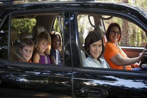 a woman driving a car taking some kids to school