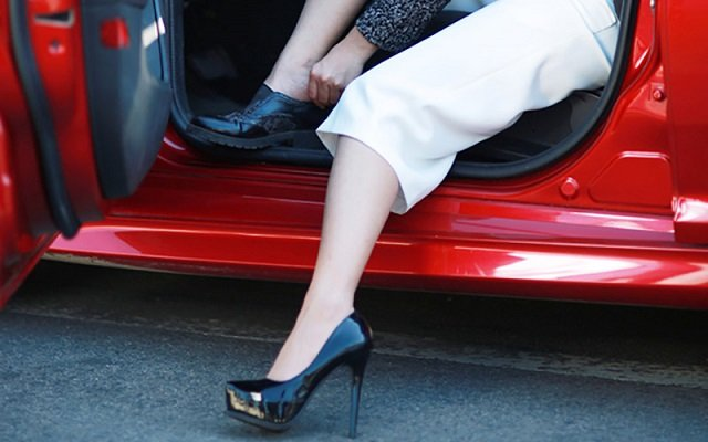 a woman wearing high heels getting out of a red car
