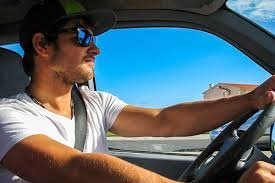 A man wearing glasses driving a car