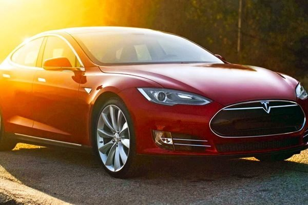 A red Tesla parked under the sun light