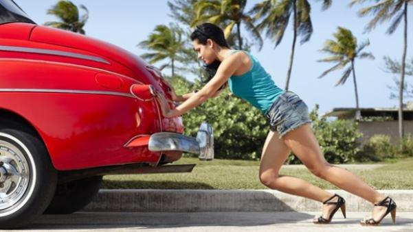 a girl pushing a car