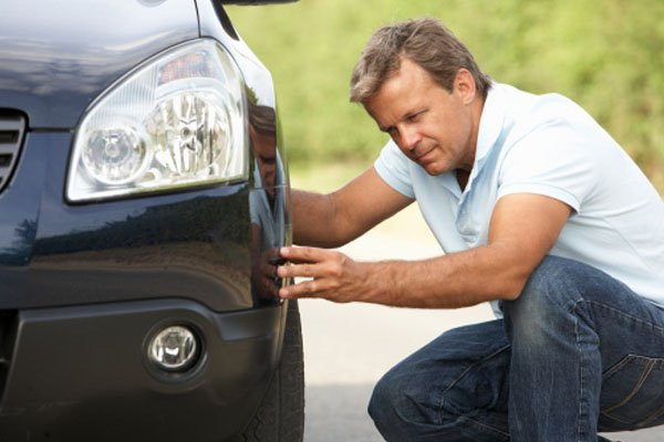 a man checking his car's tires