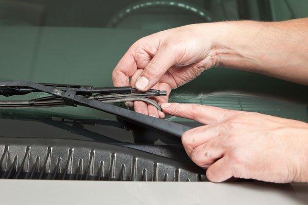 a man checking his car's wiper blades