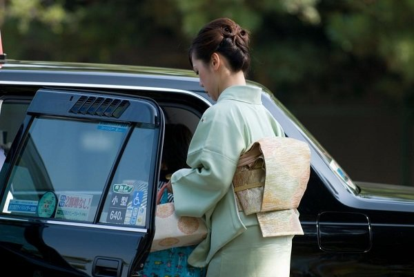 A Japanese woman getting in a taxi