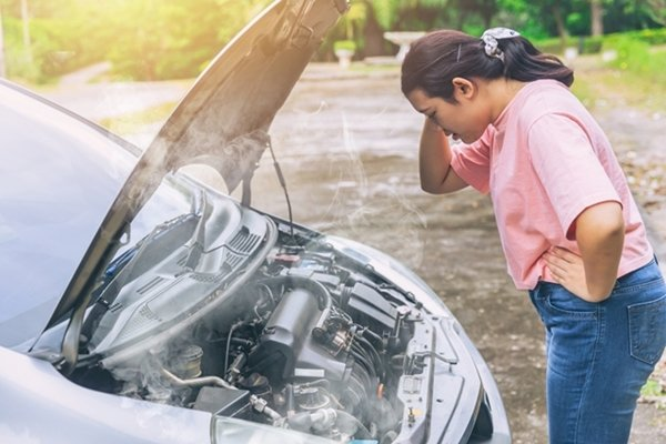 a woman standing in front of an overheated car engine