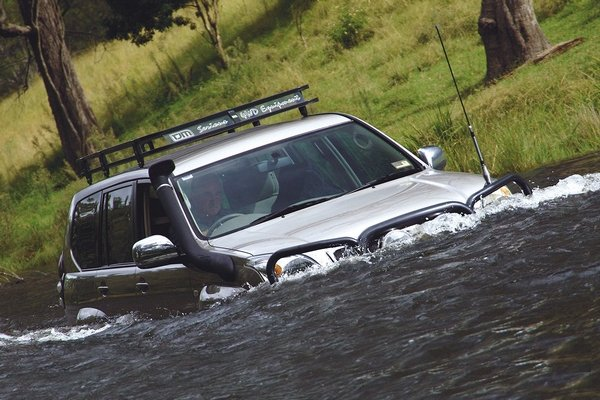 car with snorkel wading through flood